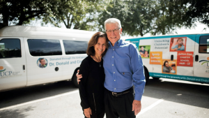 A man and a woman smiling in front of two UCP vans.
