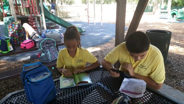 A boy and a girl seated at a picnic table reading