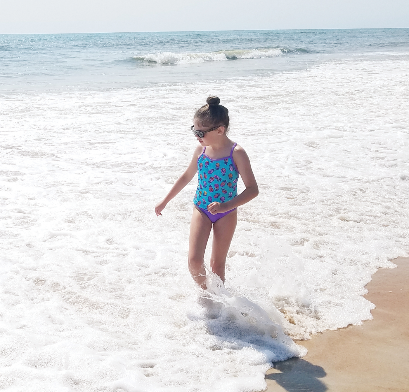 A little girl standing in the water at the beach,