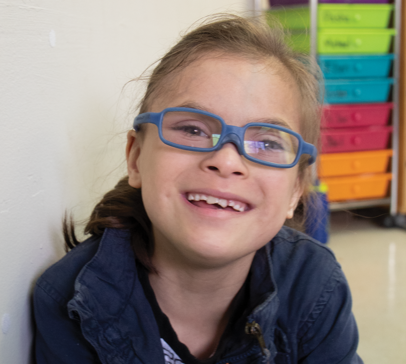 A young girl with glasses smiling at the camera.