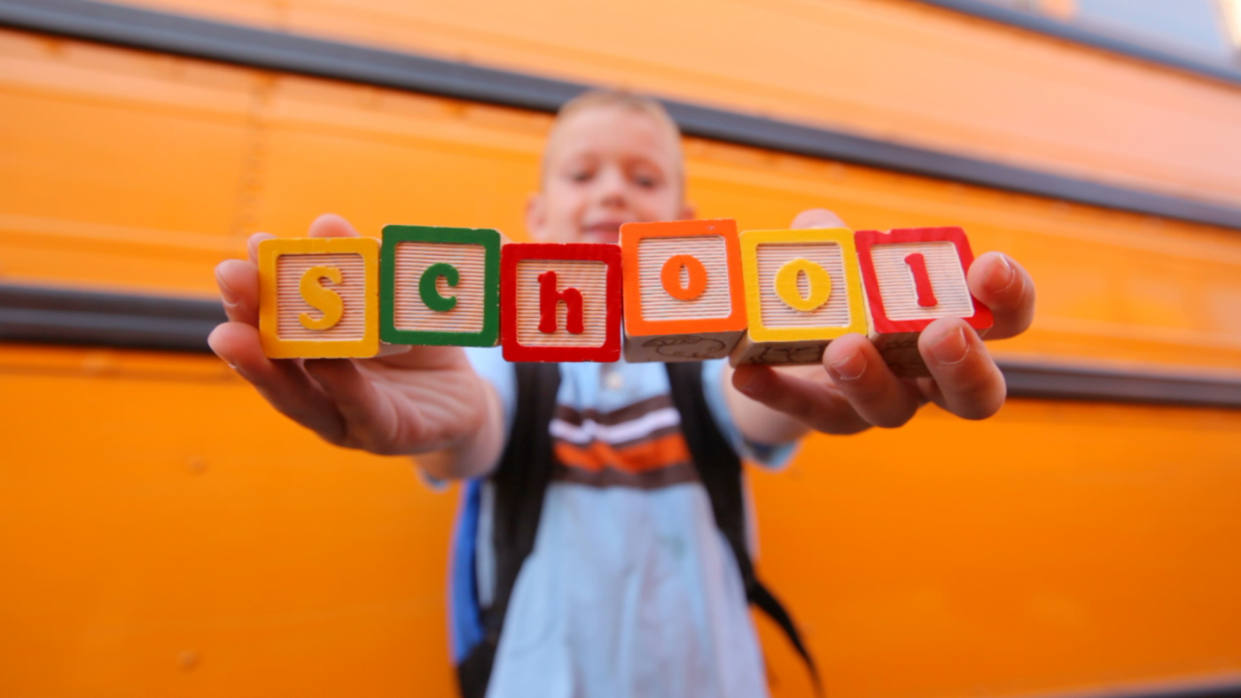 """Young boy with backpack holding building blocks spelling """"School."""""""