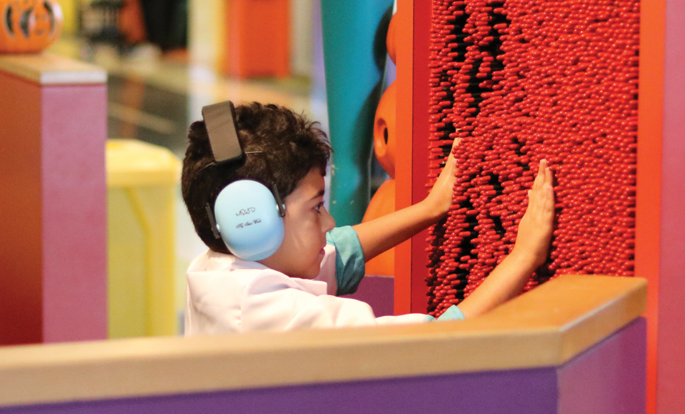 A young boy wearing headphones playing with sensory-safe equipment.
