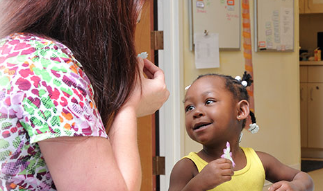 Nurse speaking to smiling young girl