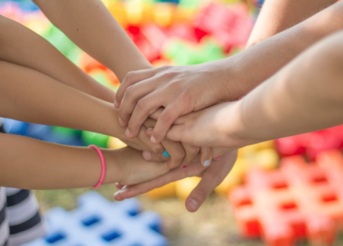 A group of children in a circle with their hands on top of one another's