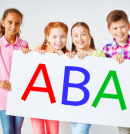 Children holding paper with ABA on it.
