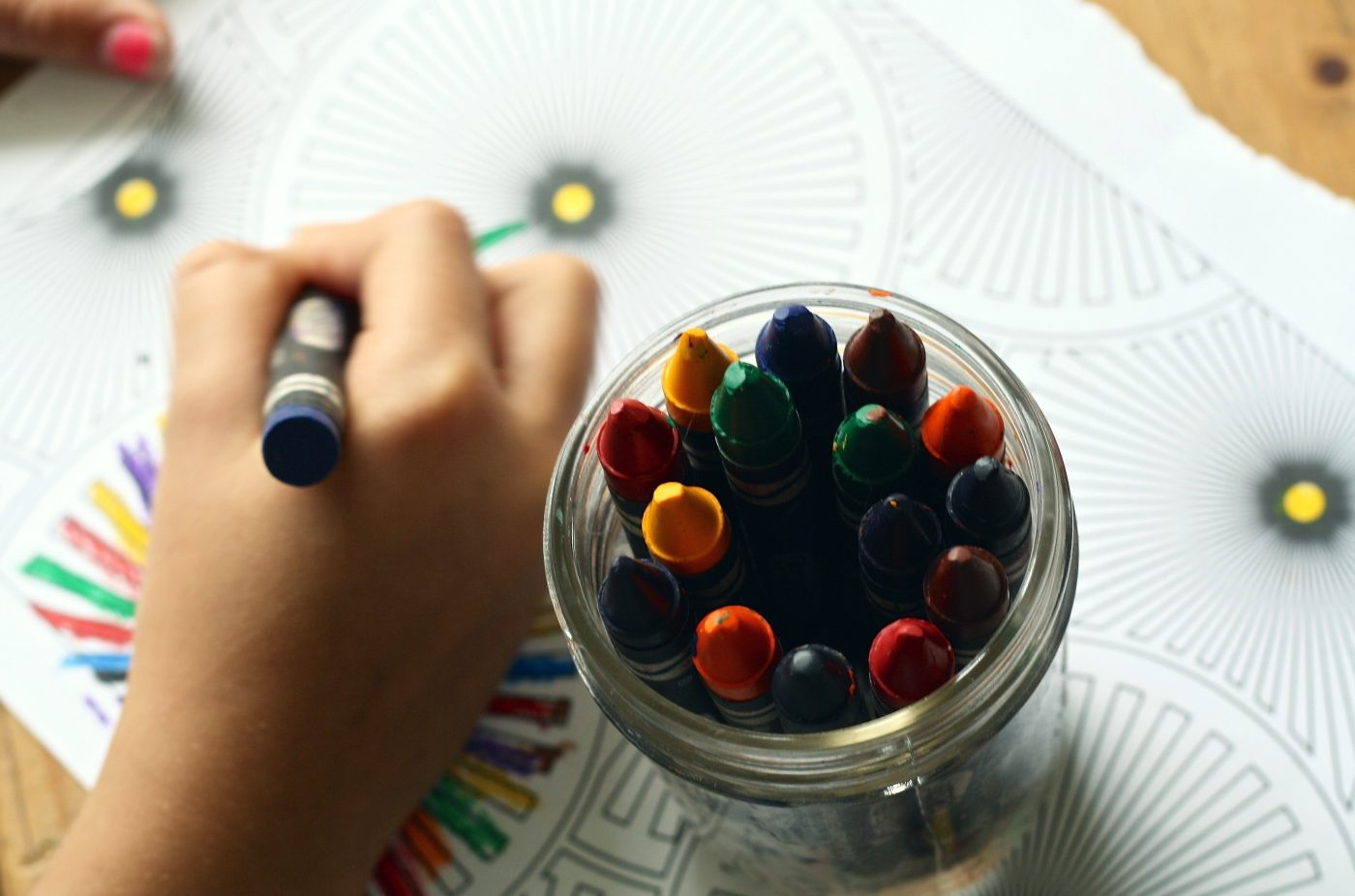 A child's hand coloring with a crayon. There is a glass jar of crayons next to the hand.