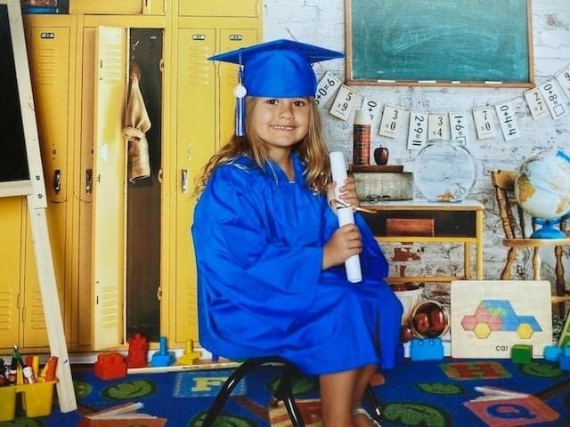 A little girl in a blue graduation cap and gown, holding a diploma and sitting on a chair in a classroom.