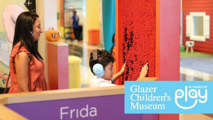 A young boy wearing headphones feeling a red patterned wall in front of his mother. In the corner is the Glazer children's museum logo.