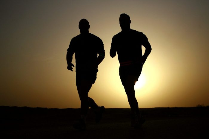 Two male silhouettes running. With the sunset in the background.