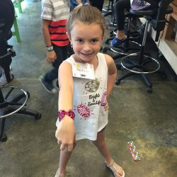 A little girl showing off her bracelet