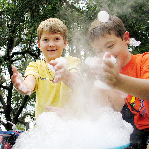 Two young boys play with a bucket of soap bubbles. In front of a group of trees.