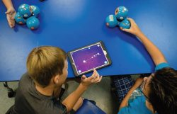 Two young children sitting at a blue table. One is using an ipad device another is holding a blue toy.