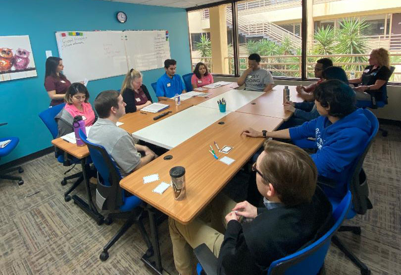 A group of students sitting around a large table. Listening to their instructor.