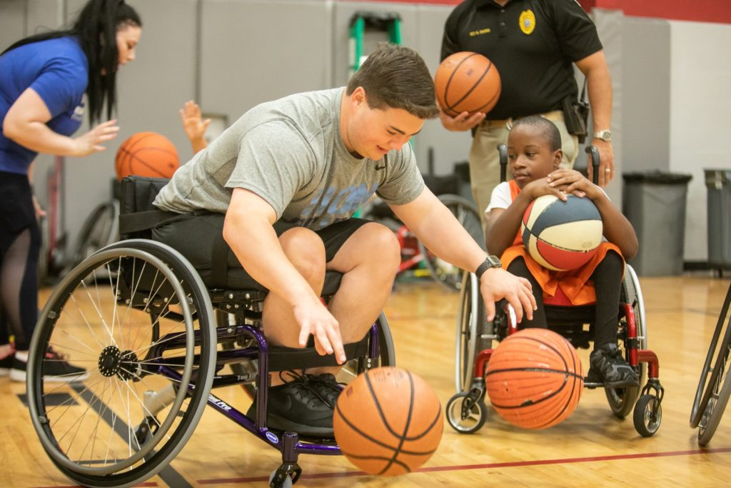 A group of kids in Wheelchairs playing basketball.