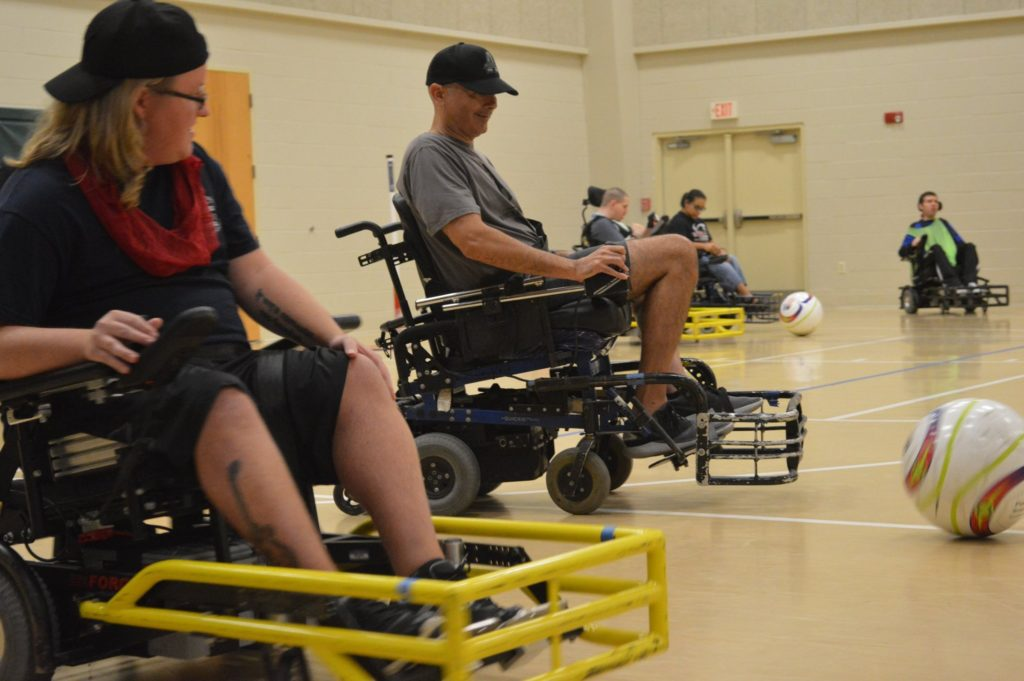 A group of people in Wheelchairs playing a game of soccer.
