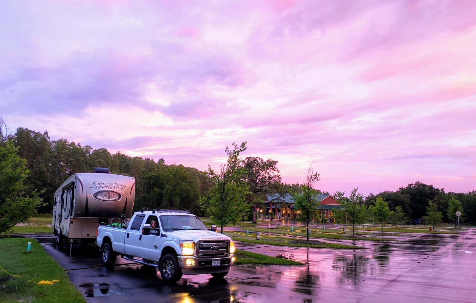 Camp Idlewild beautiful pink and purple sunset with wooded building in the background with a truck and camper in a parking lot.
