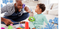 A father holding a purple ring up to his eye. In front of his baby who is holding a green ring.
