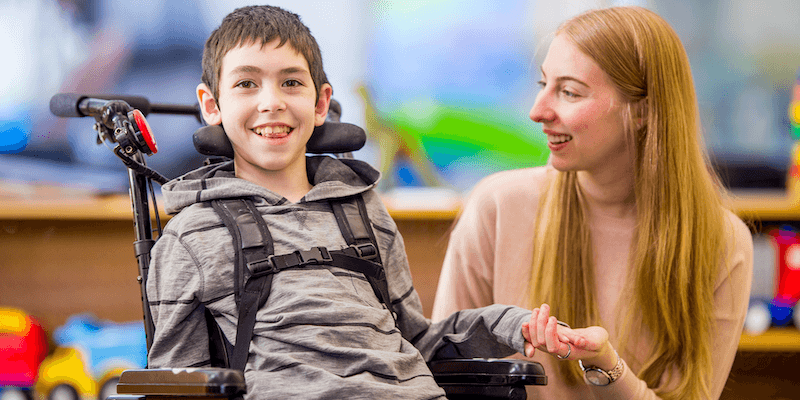 A handicapped child smiling and holding a woman's hand