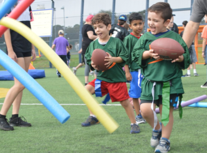 2 young happy boys both wearing green jerseys both holding a football at a flag football field.