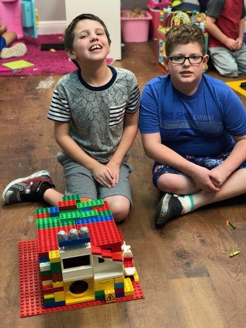 Two children sitting by an assembled lego building.